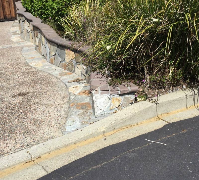 The end of the wall curves into the driveway. This is an obstacle that has obviously been hit a few times.